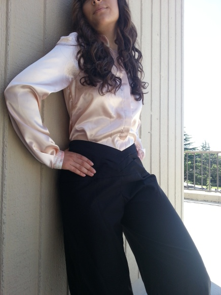 Black satin pants with layered waistband, paired with a silk blouse.